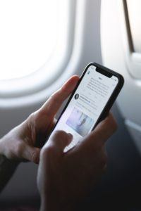Online Presence - person on phone on airplane using Twitter
