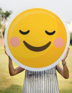 Online Presence - woman holding smiling face emoji poster