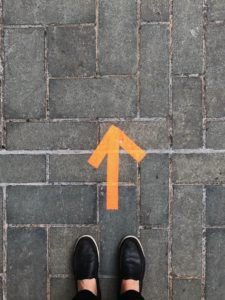 Branding - pair of feet standing in front of orange arrow on ground