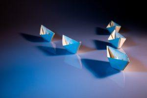 leadership - paper boats on white table